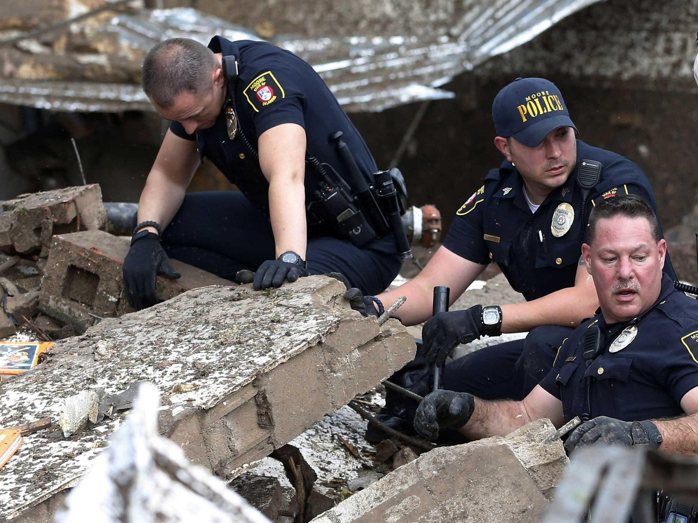 Moore police dig through the rubble of the Plaza Towers Elementary School following a tornado in Moore, Okla., Monday, May 20, 2013  Photo Copyright AP
